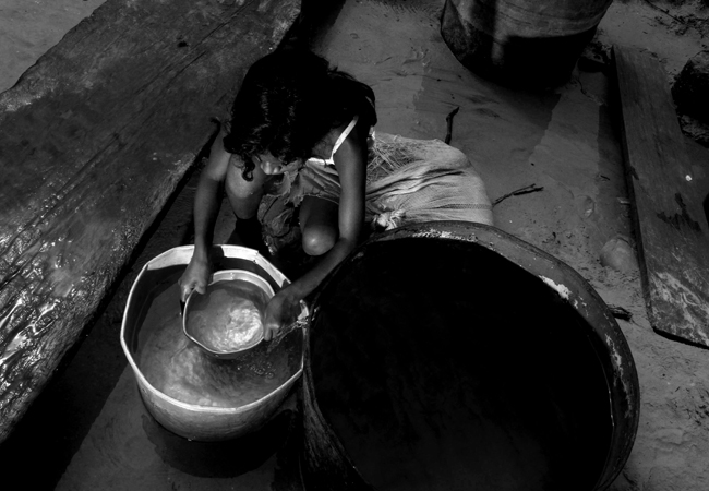 MANAUS AM 26 10 2010 RECORDE VAZANTE- SECA AMAZONAS. Marleice Oliveira 13 anos busca agua na cacimba, única fonte de água potável da comunidade de Bacuri, em Tefé. Chegada da ajuda humanitária a   a comunidade de Bacuri em Tefé, onde foram distribuidas 1280 cestas de alimentos e kits de higiene para 64 famílias que vivem praticamnte isoladas.   A Defesa Civil do Amazonas começou a distribuição de kits de alimentação em 6 comunidades da região do Médio Solimões, serão 130 toneladas em 6 nas comunidades mais iisoladas onde só é possível chegar por meio de helicóptero do Exercito. A operação feita pelo 4o_ Batalhão de Aviação do Exército BAVEX em comunidaes de Tefé, Alvarães e Uarini. (Foto Alberto Cesar Araujo)