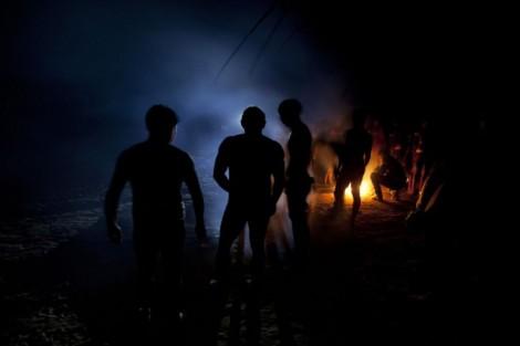 """Kamaiuras durante a cerimônia do Kwarup se reúnem juntos as fogueiras para cultuar seus mortos. Parque indígena Xingu. Kuarup O Kwarup (nome do ritual na língua kamaiurá) é considerado o grande emblema do Alto Xingu e trata-se de uma cerimônia funerária, que envolve mitos de criação da humanidade, a classificação hierárquica nos grupos, a iniciação das jovens e as relações entre as aldeias. Ao longo dos meses que se seguem até o encerramento ocorrem, não necessariamente todos os dias, dois tipos de danças e o toque de longas flautas (uruá, na língua dos Kamaiurá), sempre retribuídos com oferecimento de alimentos pelos """"donos"""" do Kwarup. O foco de orientação dessas atividades rituais é sempre a cerca sobre a sepultura. No pátio da aldeia promotora do rito, cada falecido homenageado é representado por uma seção de tronco de cerca de dois metros. São de uma espécie vegetal que tem distintas denominações conforme as diferentes línguas xinguanas. Os Kamaiurá a chamam de Kwarup, a mesma madeira com que o herói mítico fez as mulheres que enviou para se casarem com o jaguar. Os troncos são colocados um ao lado do outro, de pé, embutidos em buracos de 50 cm de fundo. São pintados e ornamentados com adornos plumários e cintos masculinos. A única distinção entre os troncos que representam homens e os que representam mulheres é que os primeiros são guarnecidos com mechas de algodão não fiado. Também os homens comuns falecidos têm direito a ser representados por troncos, porém menos grossos e com ornamentação mais simples. Os espíritos dos mortos homenageados ficam junto aos troncos na última noite do rito e a isto se reduz a sua participação. Ao anoitecer, acendem-se fogueiras diante de cada tronco do Kwarup. Enquanto os moradores da aldeia anfitriã se revezam, velando os troncos e chorando os falecidos homenageados, os visitantes, cada acampamento por sua vez, entram na aldeia, trazendo achas de pindaíba para remanejar as fogueiras, numa cena movimentada e tensa. Foto Paulo Sa"""
