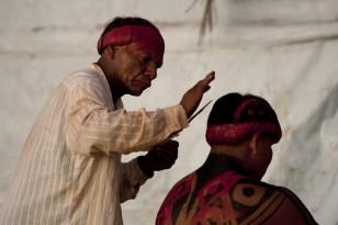 Lutadores de diversas aldeias se preparam para o Huka-huka. Huka-hukaLuta corporal que na terminologia kamaiurá lembra os gritos dos lutadores ao se defrontarem imitando o rugido da onça. Os anfitriões enfrentam uma aldeia convidada de cada vez, começando por lutas individuais de campeıes reconhecidos. Seguem-se lutas simultâneas de vários pares de rivais, até as lutas dos muito jovens. Os lutadores se defrontam batendo o pé direito no chão, dando voltas no sentido dos ponteiros do relógio, com o braço esquerdo estendido e o direito retraído, enquanto gritam alternadamente: hu! ha! hu! ha! Até que chocam as mãos direitas e enlaçam o pescoço do adversário com a esquerda. A luta, que pode durar poucos segundos, termina quando um dos adversários é derrubado, o que não tem que ocorrer literalmente, bastando que a parte posterior de um de seus joelhos seja agarrada pela mão do outro, o que é considerado condição suficiente para provocar-lhe a queda. As aldeias convidadas não lutam entre si. Os enfeites dos troncos do Kwarup podem ser dados aos lutadores vencedores e também aos dois tocadores de maracá.. Querência, Mato Grosso, Brasil. 26/07/2015 Fonte: ISA