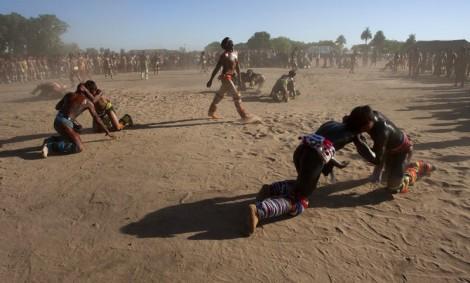 Lutador sai de cabeça erguida após vencer uma luta do Huka-huka. Huka-huka Luta corporal que na terminologia kamaiurá lembra os gritos dos lutadores ao se defrontarem imitando o rugido da onça. Os anfitriões enfrentam uma aldeia convidada de cada vez, começando por lutas individuais de campeıes reconhecidos. Seguem-se lutas simultâneas de vários pares de rivais, até as lutas dos muito jovens. Os lutadores se defrontam batendo o pé direito no chão, dando voltas no sentido dos ponteiros do relógio, com o braço esquerdo estendido e o direito retraído, enquanto gritam alternadamente: hu! ha! hu! ha! Até que chocam as mãos direitas e enlaçam o pescoço do adversário com a esquerda. A luta, que pode durar poucos segundos, termina quando um dos adversários é derrubado, o que não tem que ocorrer literalmente, bastando que a parte posterior de um de seus joelhos seja agarrada pela mão do outro, o que é considerado condição suficiente para provocar-lhe a queda. As aldeias convidadas não lutam entre si. Os enfeites dos troncos do Kwarup podem ser dados aos lutadores vencedores e também aos dois tocadores de maracá.. Querência, Mato Grosso, Brasil. 26/07/2015 Fonte: ISA